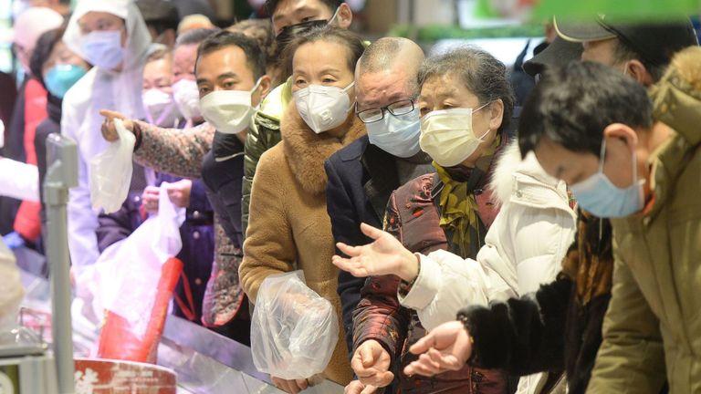 Cizme în măști de protecție la un supermarket din Wuhan